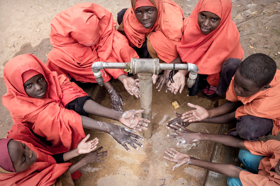 A group of kids wearing red garments hold out their hands underneath a spout of water. The device will help improve water sanitation and hygiene.