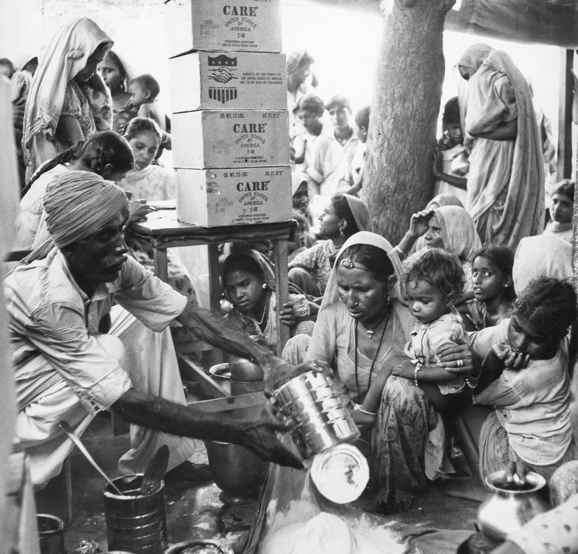 An Indian man wearing a headscarf pours flour out of a large can and into a bag. A mother and her young child watch. Behind them is a large group of men, women, and children sitting and standing. Four large CARE boxes are stacked on top of a nearby table.