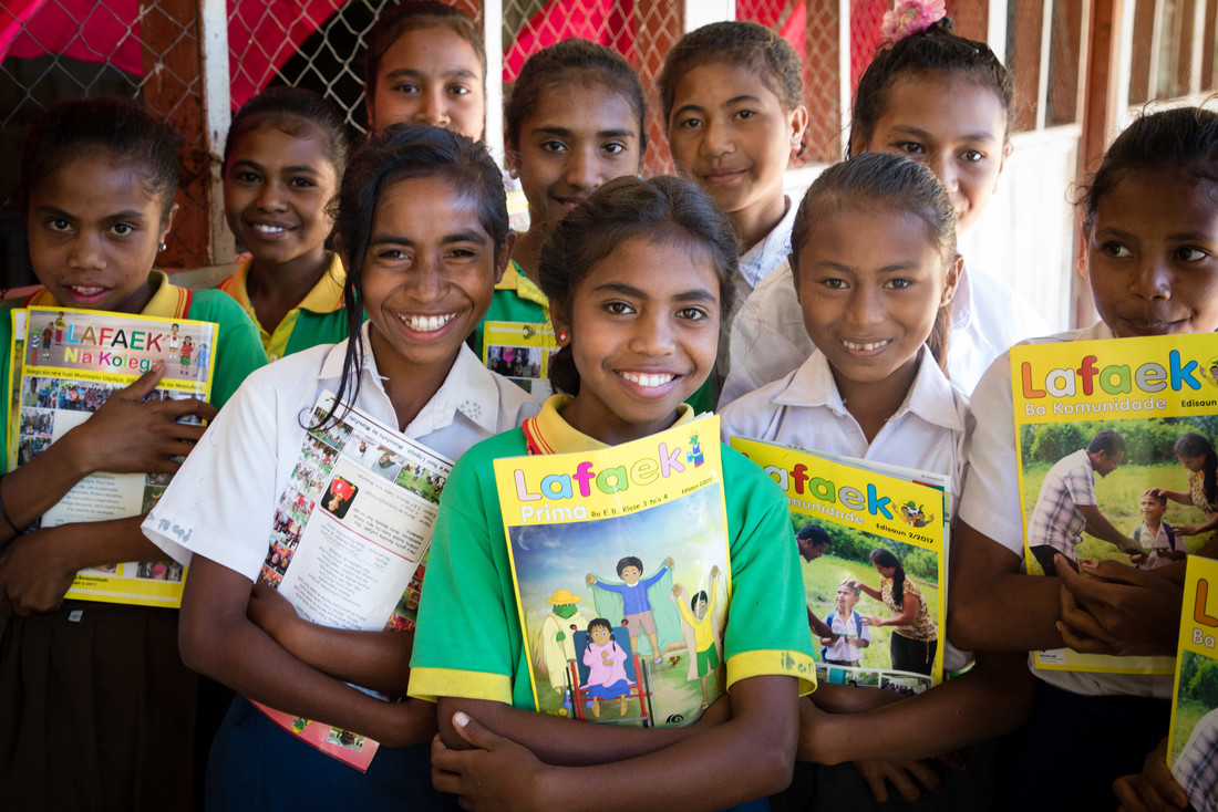 A group of girls from the local school smiling and holding copies of Lafaek Prima.