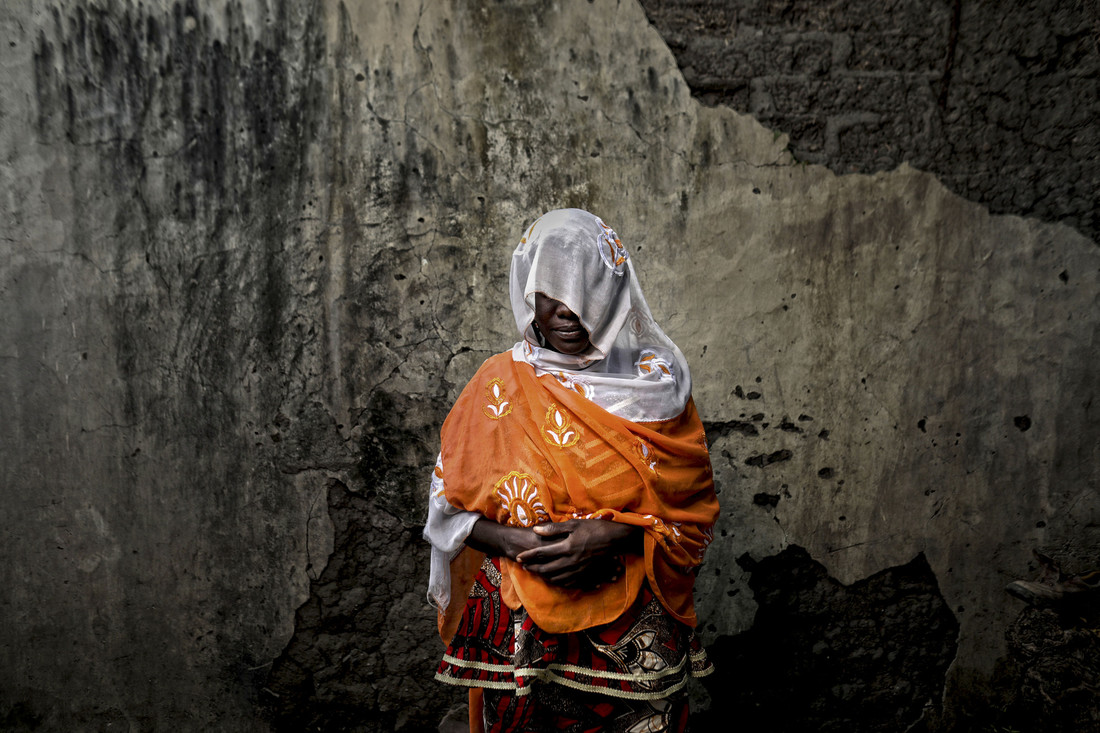 A woman stands against a wall with her hands folded in front of her. A white veil covers her face to protect her identity.
