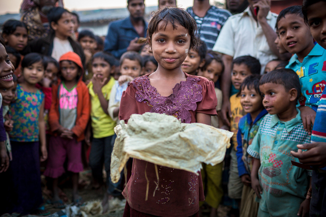 A young girl holds a cloth with a lump of clay up towards the camera. Behind her stand a large group of children.