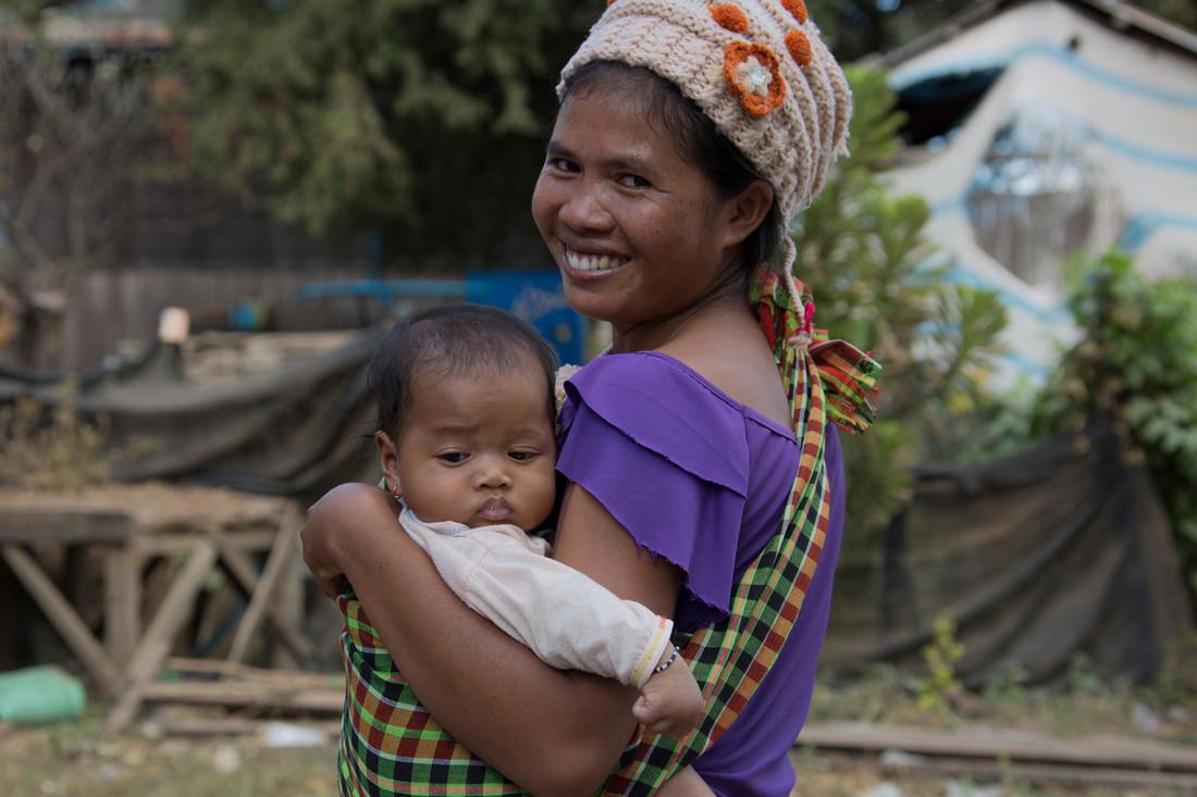 Una mujer con una camisa morada sonríe y sostiene a su bebé.