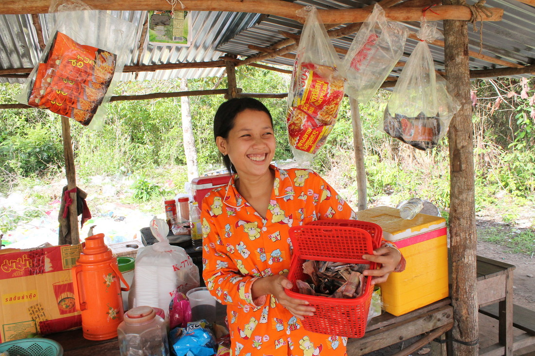A Cambodian woman wearing a bright orange patterned robe smiles while opening a red basket full of cash VSLA contributions.