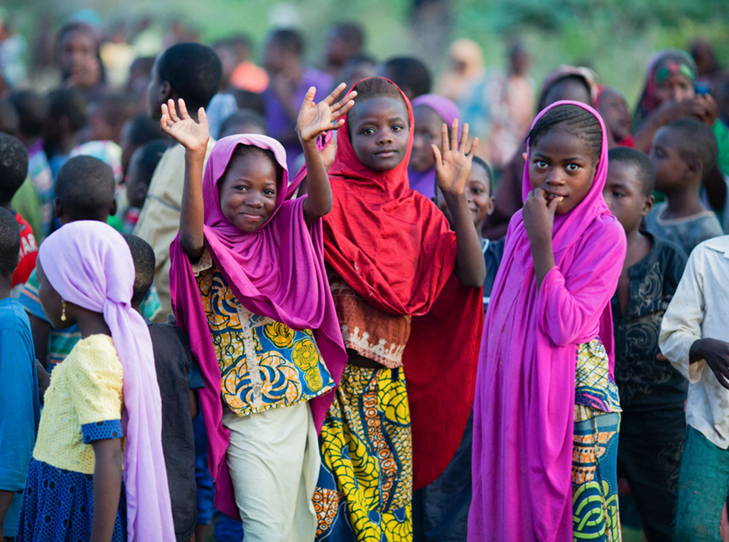 A group of children gather in the Sahel region in Niger. Three of them are smiling and waving at the camera.