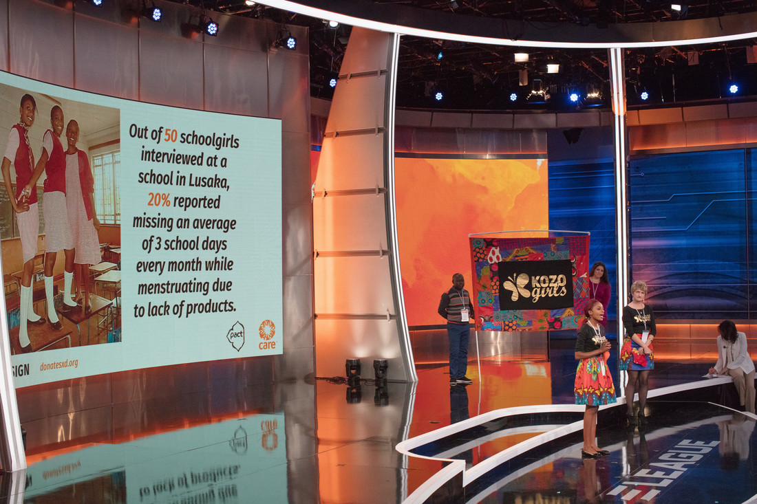 A group of women speak to a crowd. Behind them is a large screen with their business pitch as well as a board that says