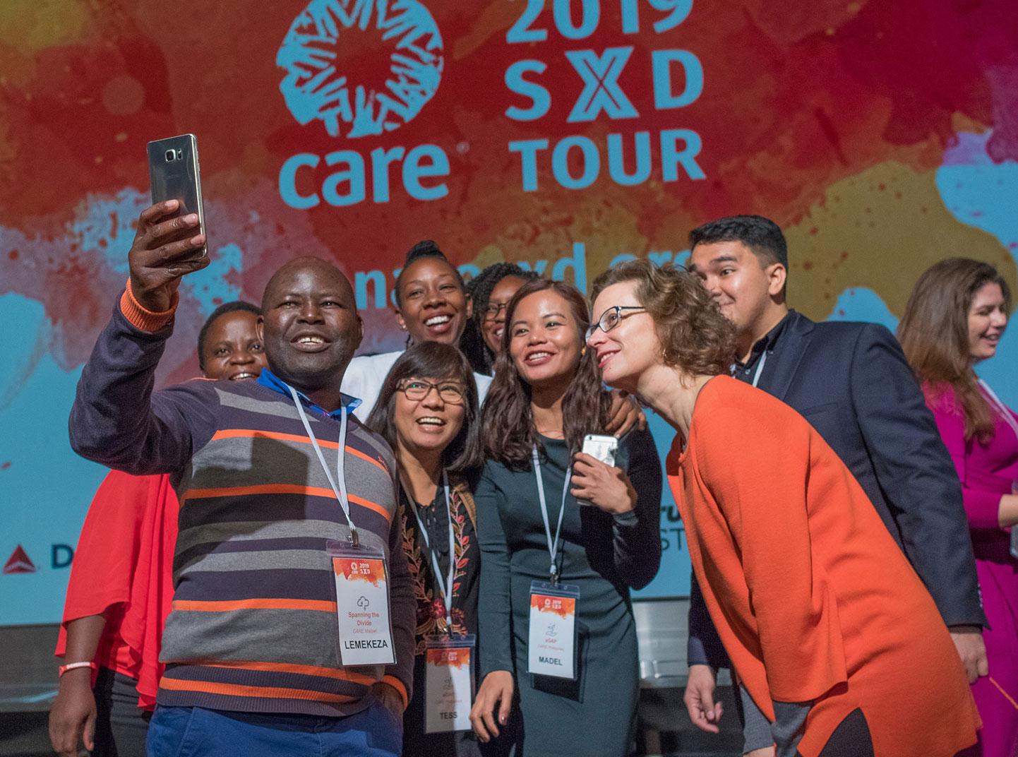 Un grupo de personas posan en el escenario con la presidenta de CARE, Michelle Nunn. Detrás de ellos hay una gran pancarta que dice