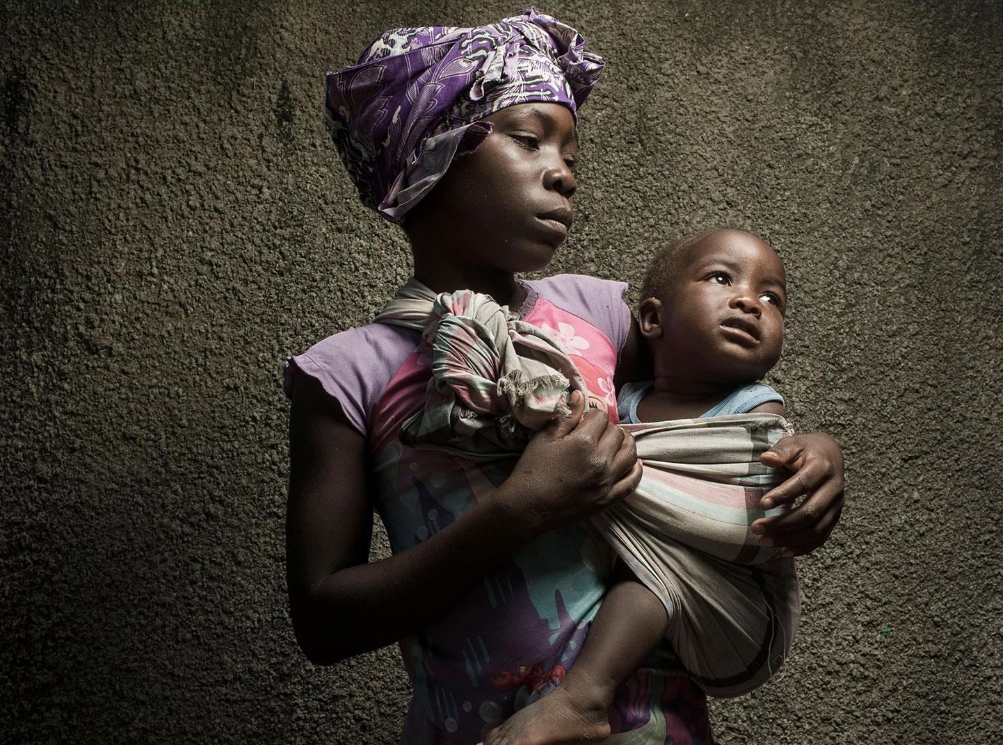 Une jeune fille tient un petit bébé dans un morceau de tissu enroulé autour de ses épaules.
