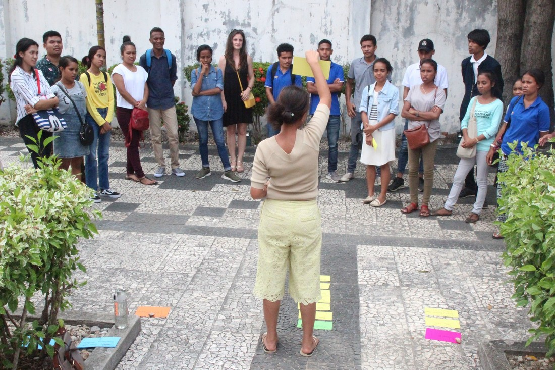 A woman stands in front of a large group of youth. She is holding up cards while they listen.