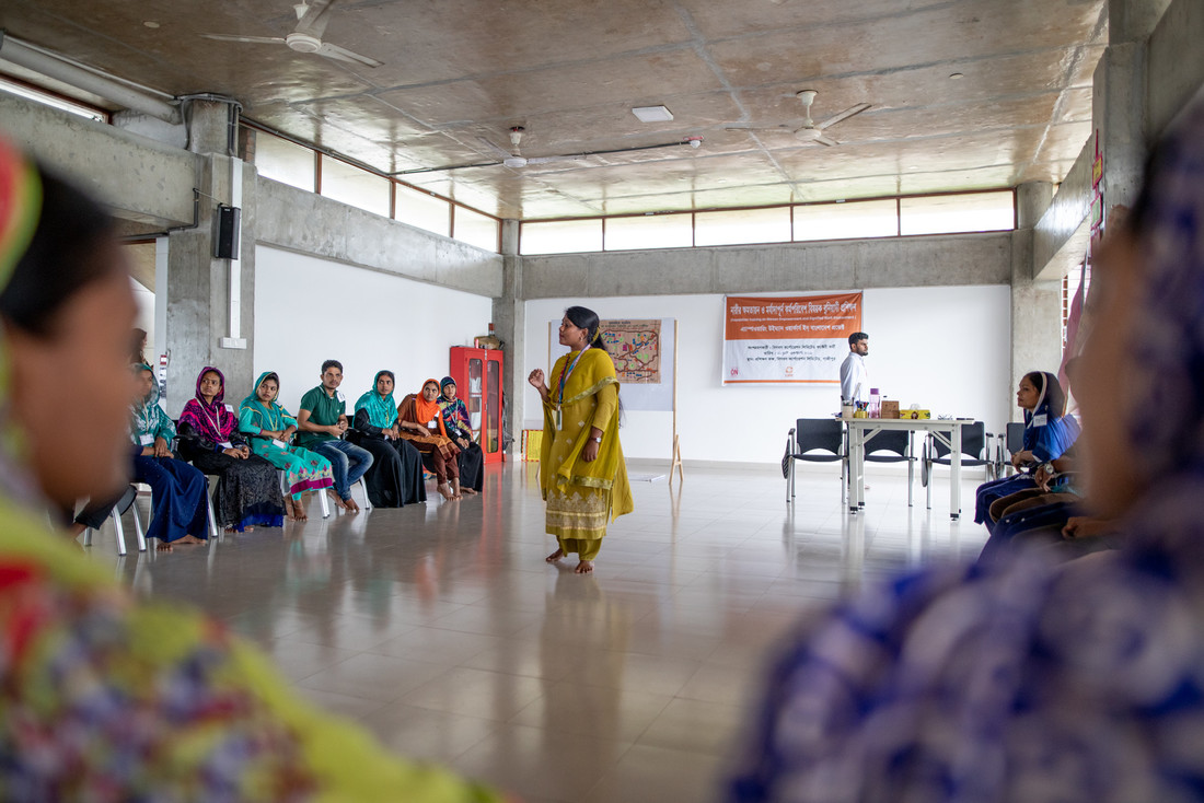 A woman wearing yellow walks around a room barefoot and speaks to a group of women.