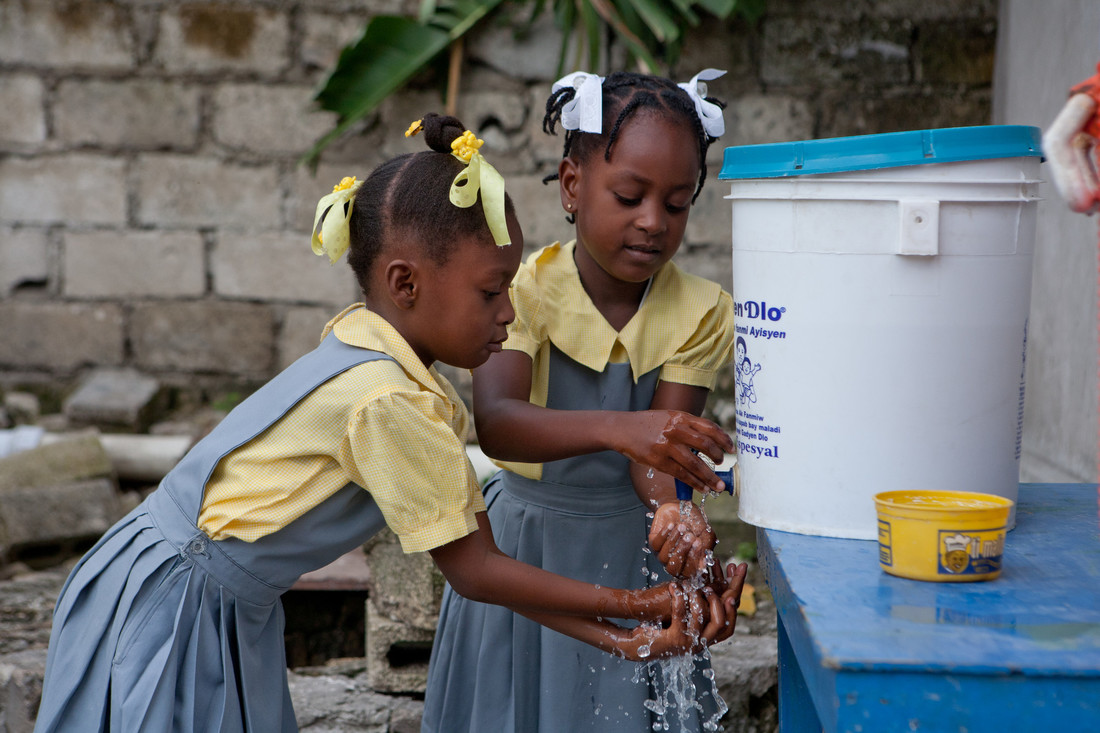 Two young Haitian girls wearing denim dresses over yellow shirts wash their hands at a station.