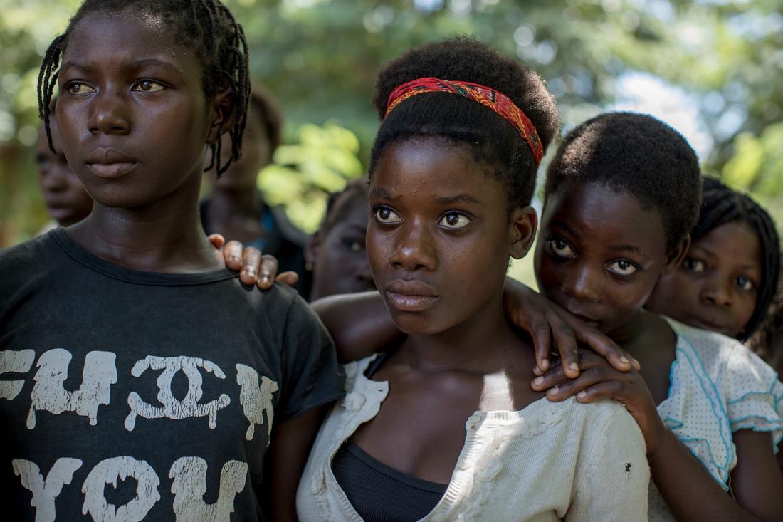 Tres chicas se paran y esperan mientras se apoyan en los hombros de la otra.