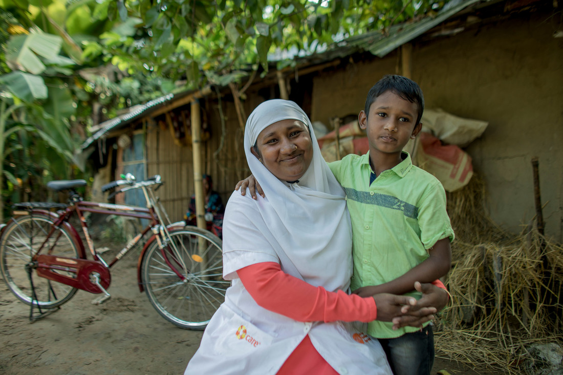 A woman sitting down smiles and hugs a young boy close to her. They are sitting in front of a small bamboo house with a bike parked outside.