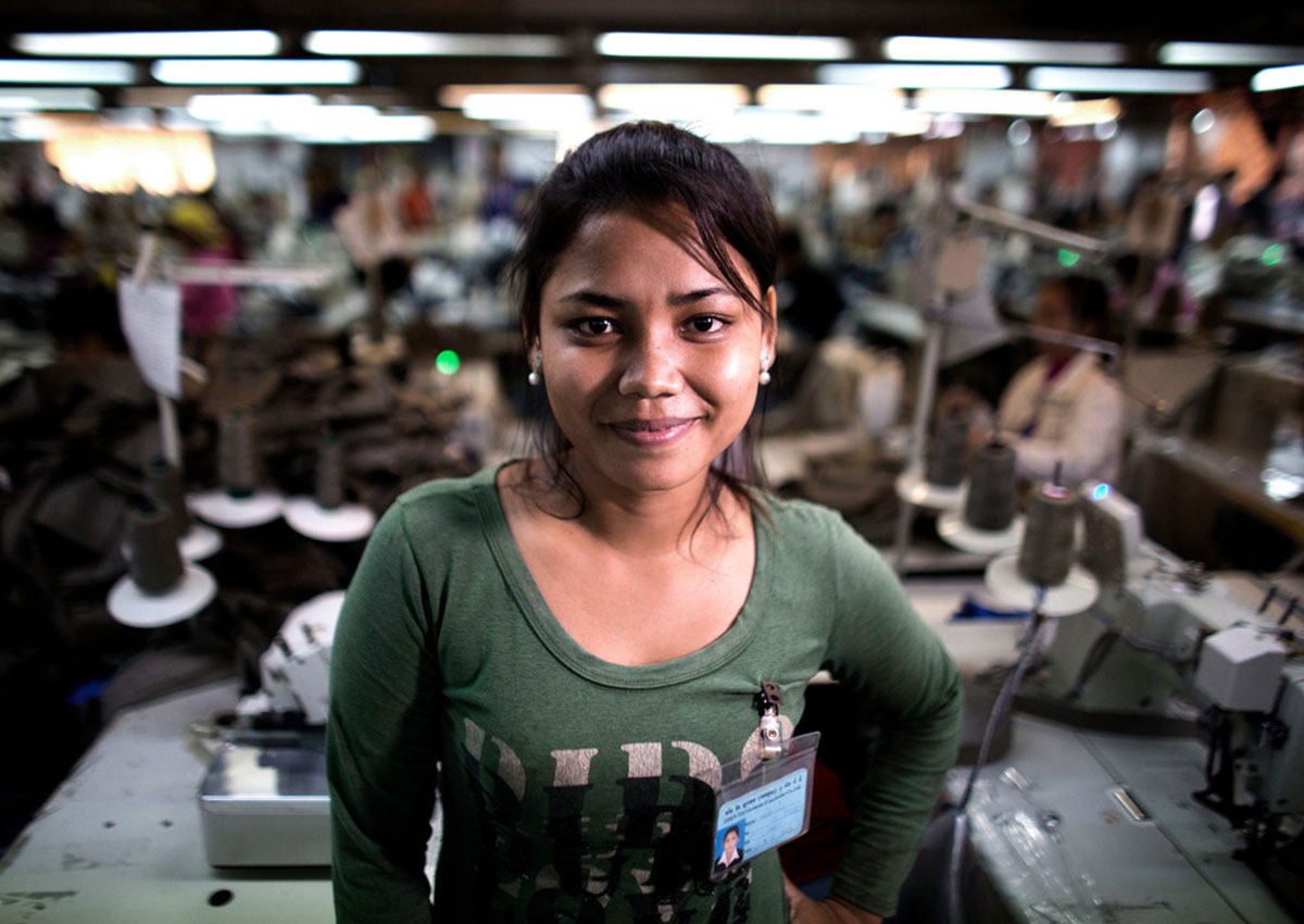 A Cambodian woman wearing a green long-sleeved shirt looks at the camera with a hand on her hip. Behind her, the interior of a garment factory is visible.