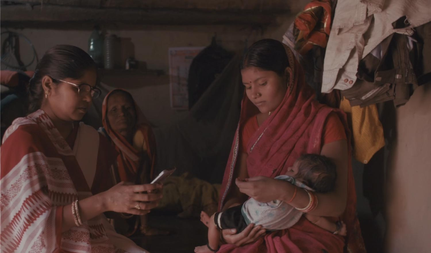 A woman holds a baby while another looks something up on a mobile phone.