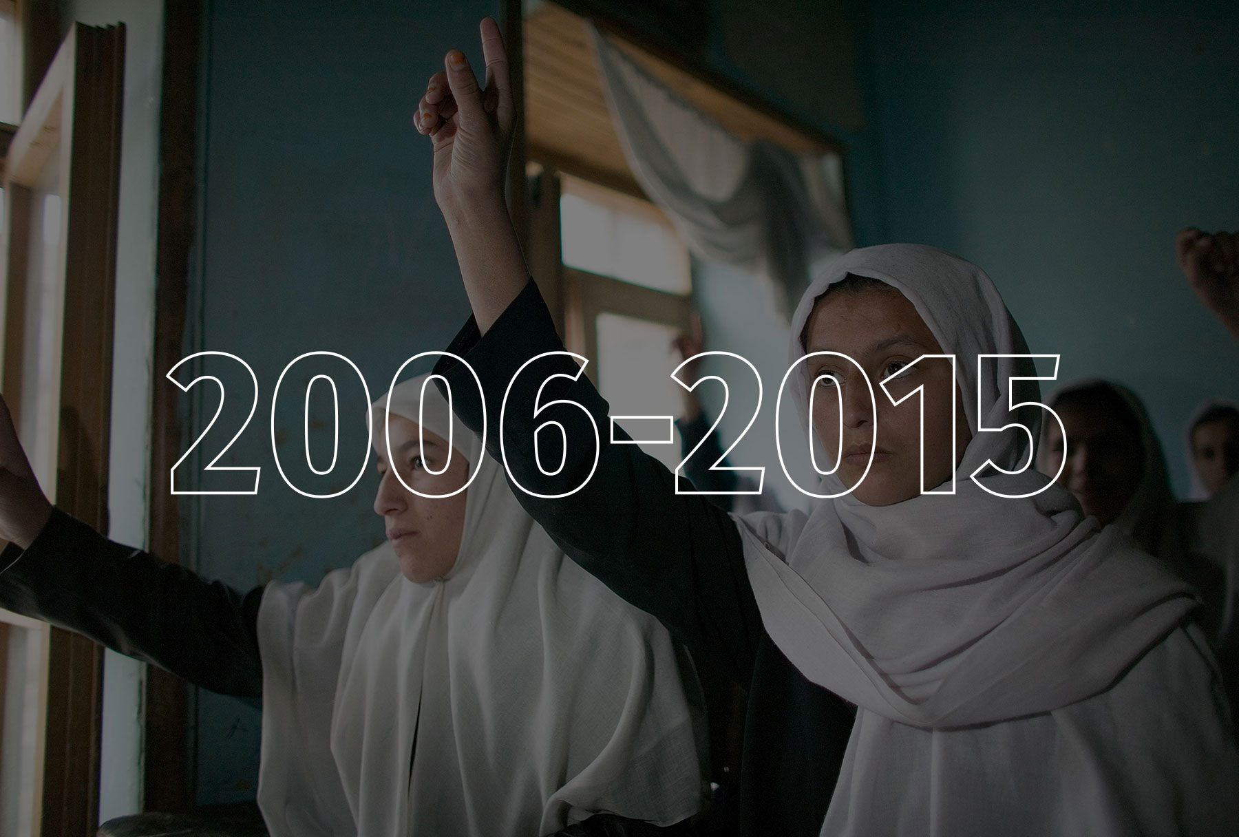 Two teenaged girls wearing dark long-sleeved shirts and white headscarves raise their right hands.