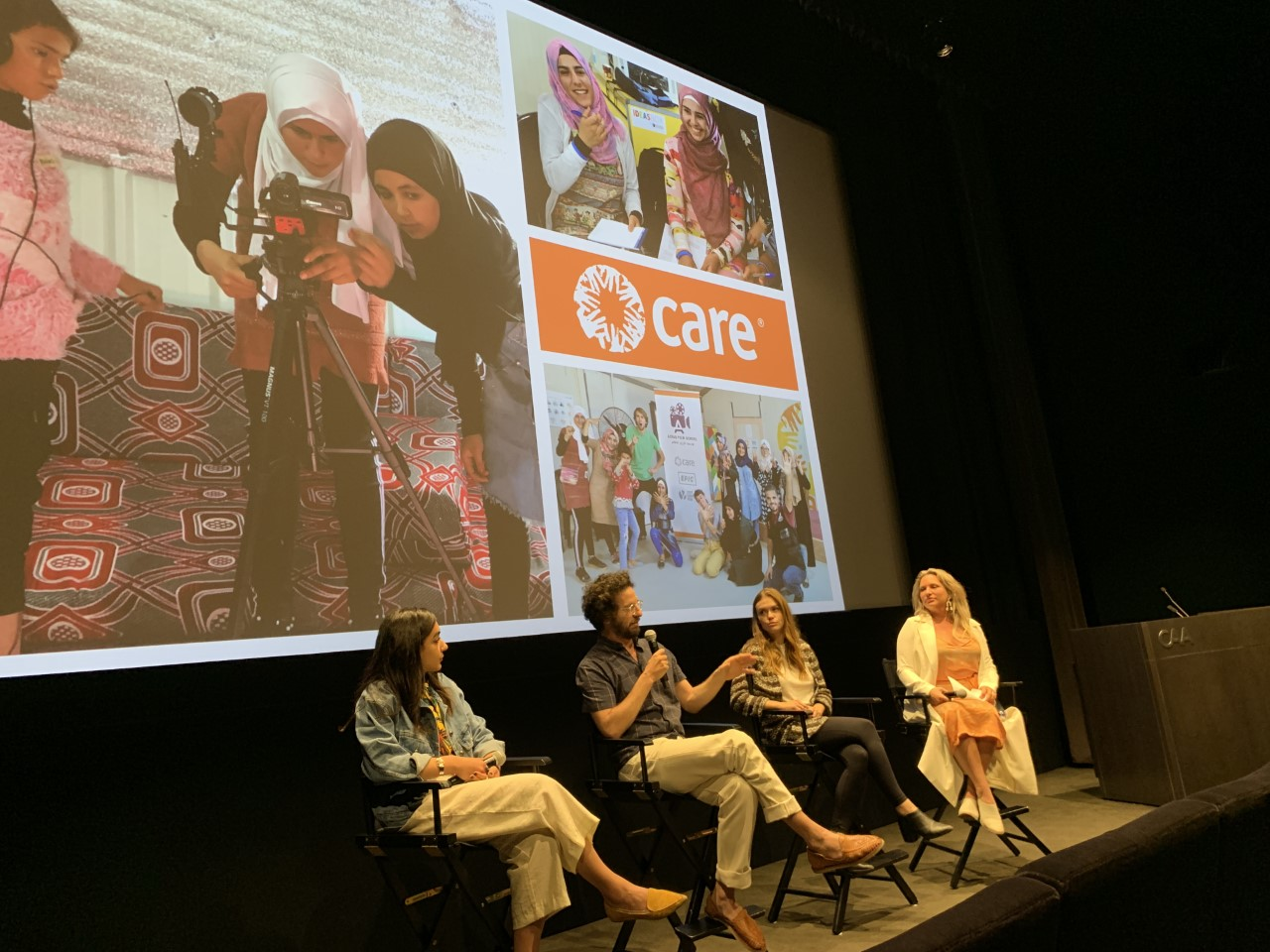 Four people sit on stage during a panel in front of a slide of images showing girls learning how to film with cameras.