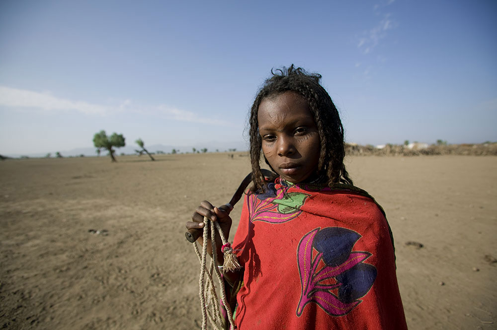 A girl wearing bright red and holding a thin rope and digging tool looks at the camera. Behind her is a wide expanse of dirt and sand with a couple of trees.