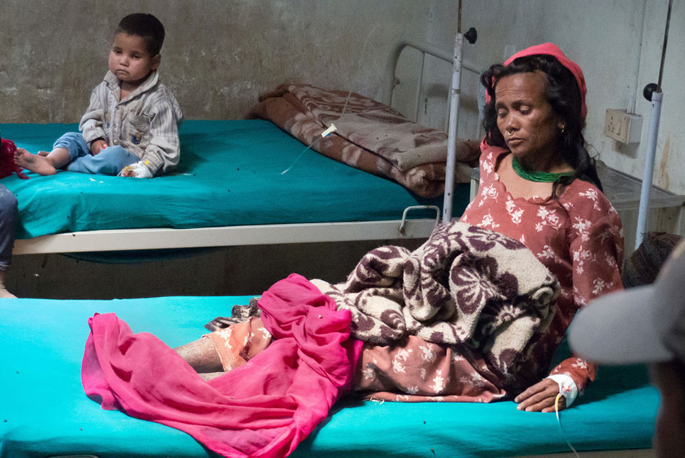 A woman and child sit in a small hospital room on two separate beds. Each is hooked up to an IV.