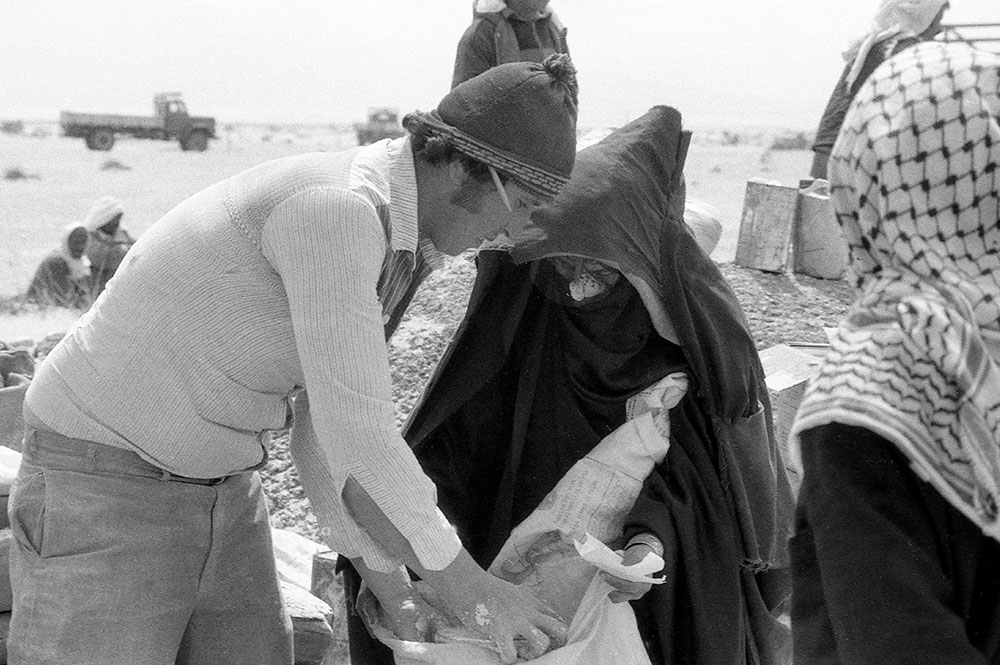 A black and white image of a man leaning over and pulling flour out of a food bag.