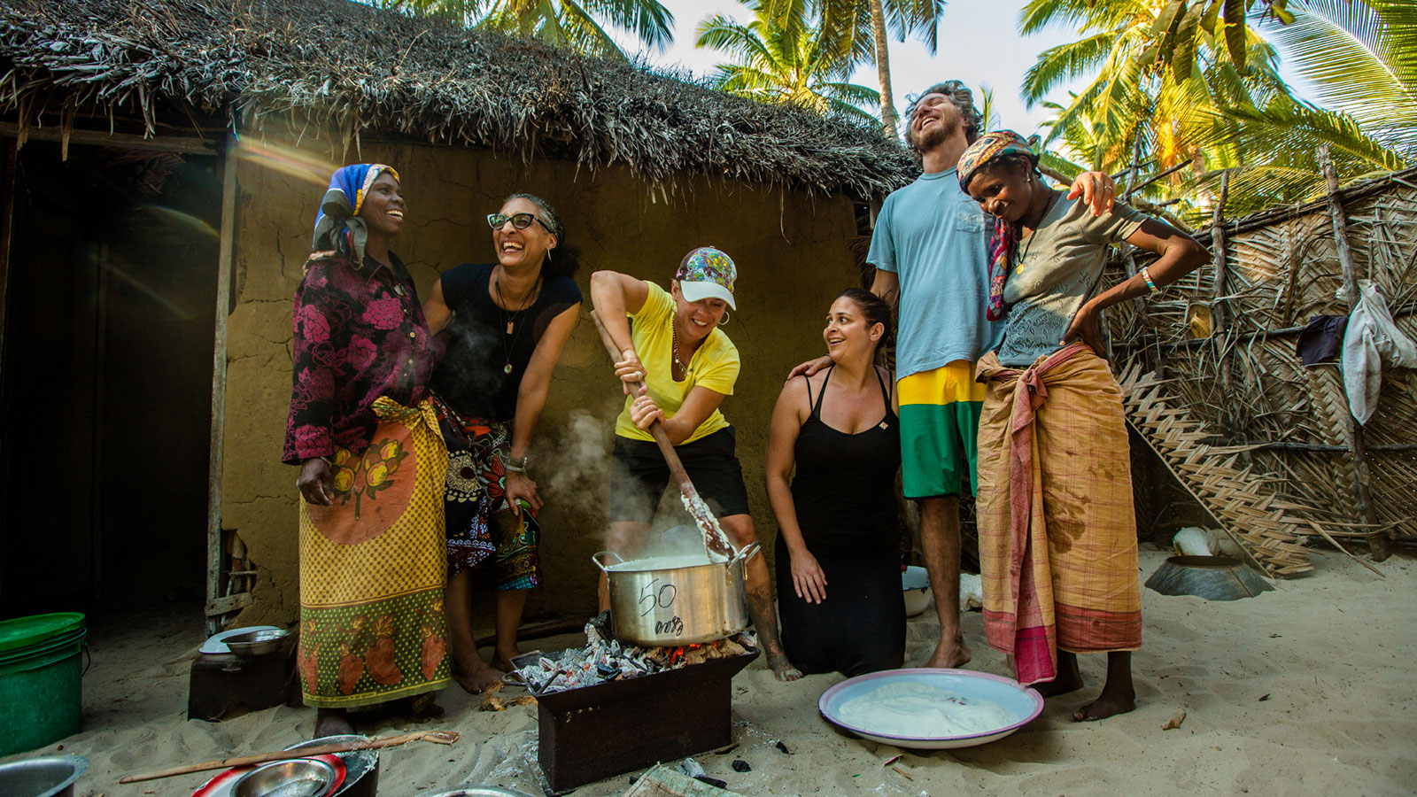 A group of people smile and laugh while cooking together.