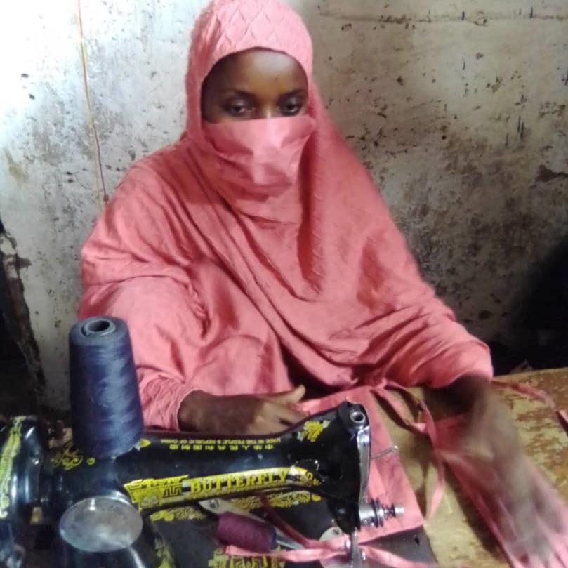 Uma mulher com uma máscara costura máscaras com uma máquina de costura no Níger.