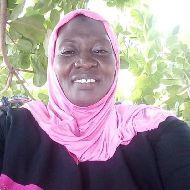 Uma mulher sorri em frente a uma árvore frondosa na Costa do Marfim.