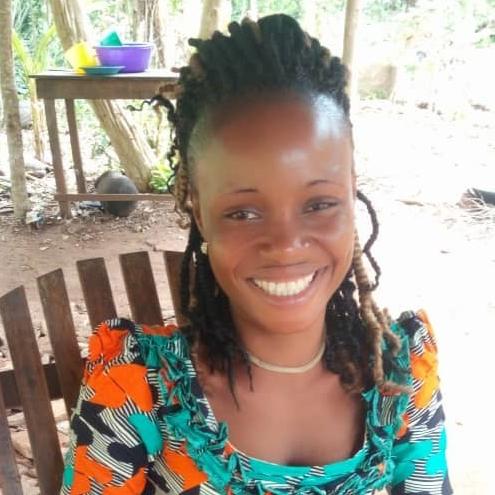 Uma mulher sorri enquanto está sentada em uma cadeira de madeira no Benin.