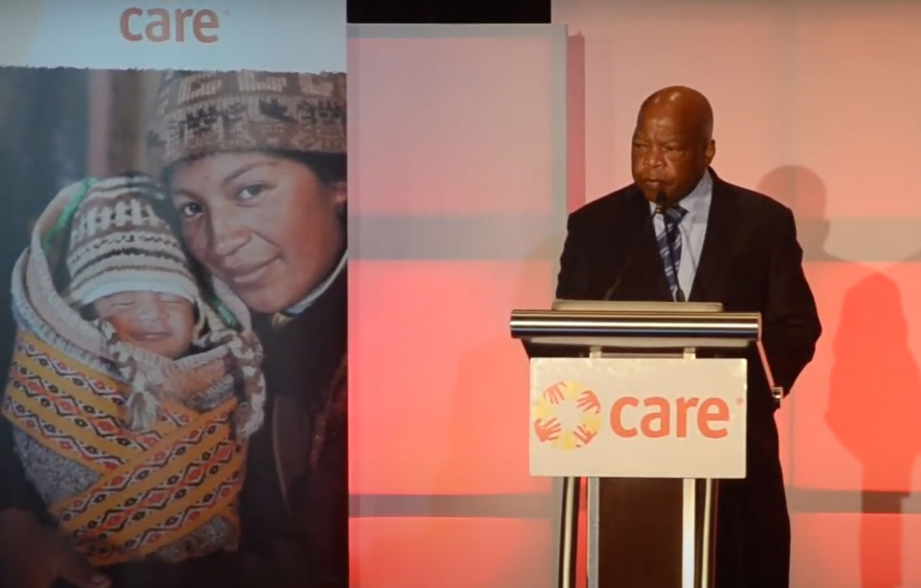 Congressman John Lewis stands a podium on stage at the 2015 CARE National Conference.