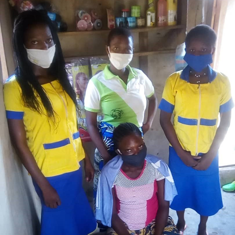A group of women in Benin sit inside a wood building with no doors while wearing masks to help prevent the spread of coronavirus.
