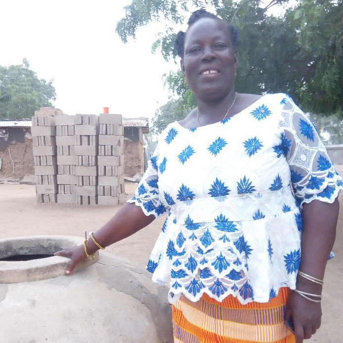 A woman in Ghana stands next to a stone workplace while in a dirt patch in from of cinder blocks.