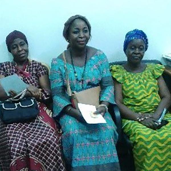 Três mulheres estão sentadas em um banco de madeira na Costa do Marfim.