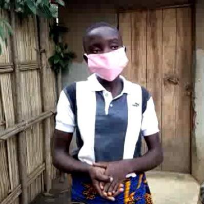 Uma mulher usa uma máscara rosa ao lado de uma cerca de madeira no Benin.