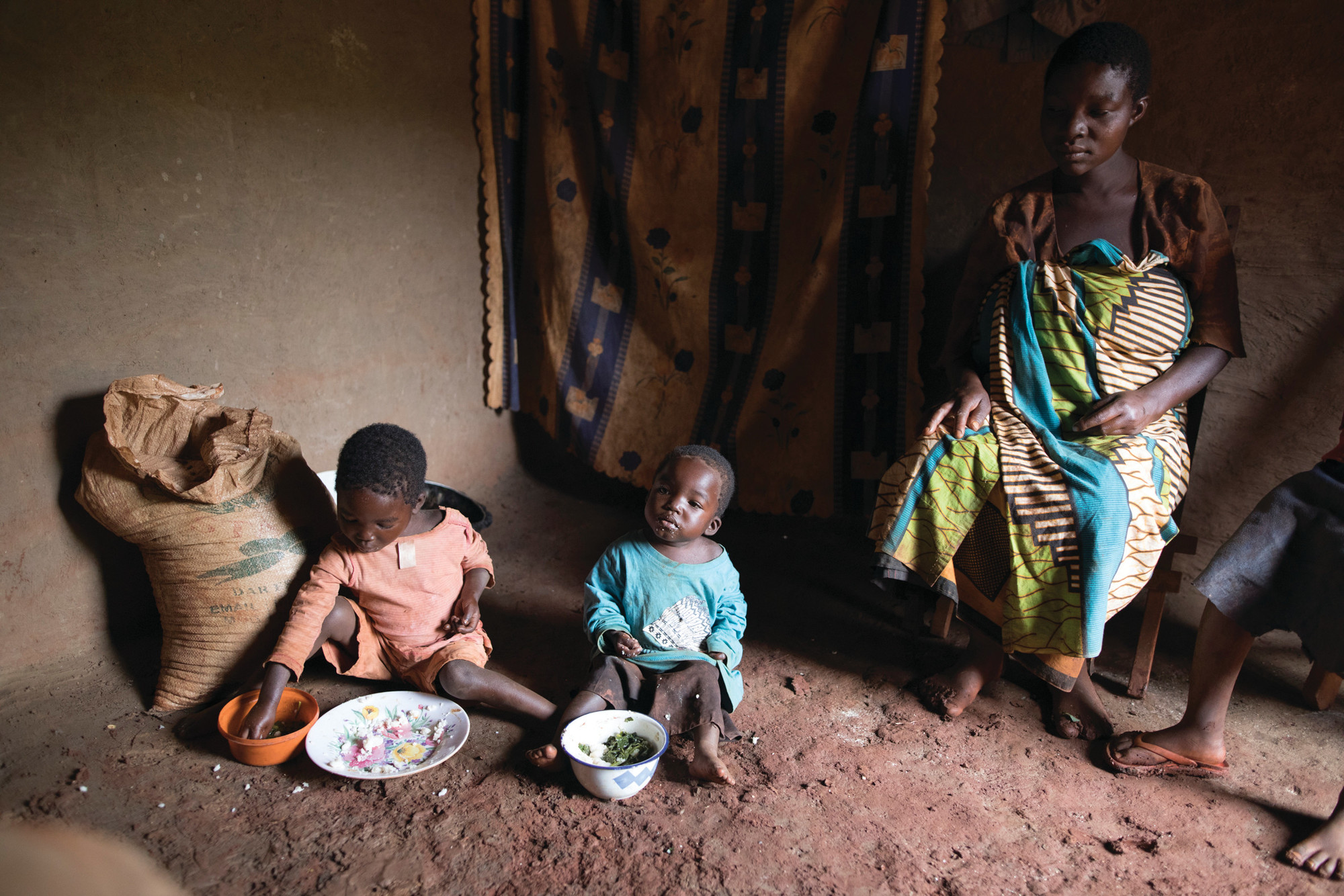 A pregnant mother sits on a wooden chair while two small children with plates of food in front of them sit on the dirt floor beside her.