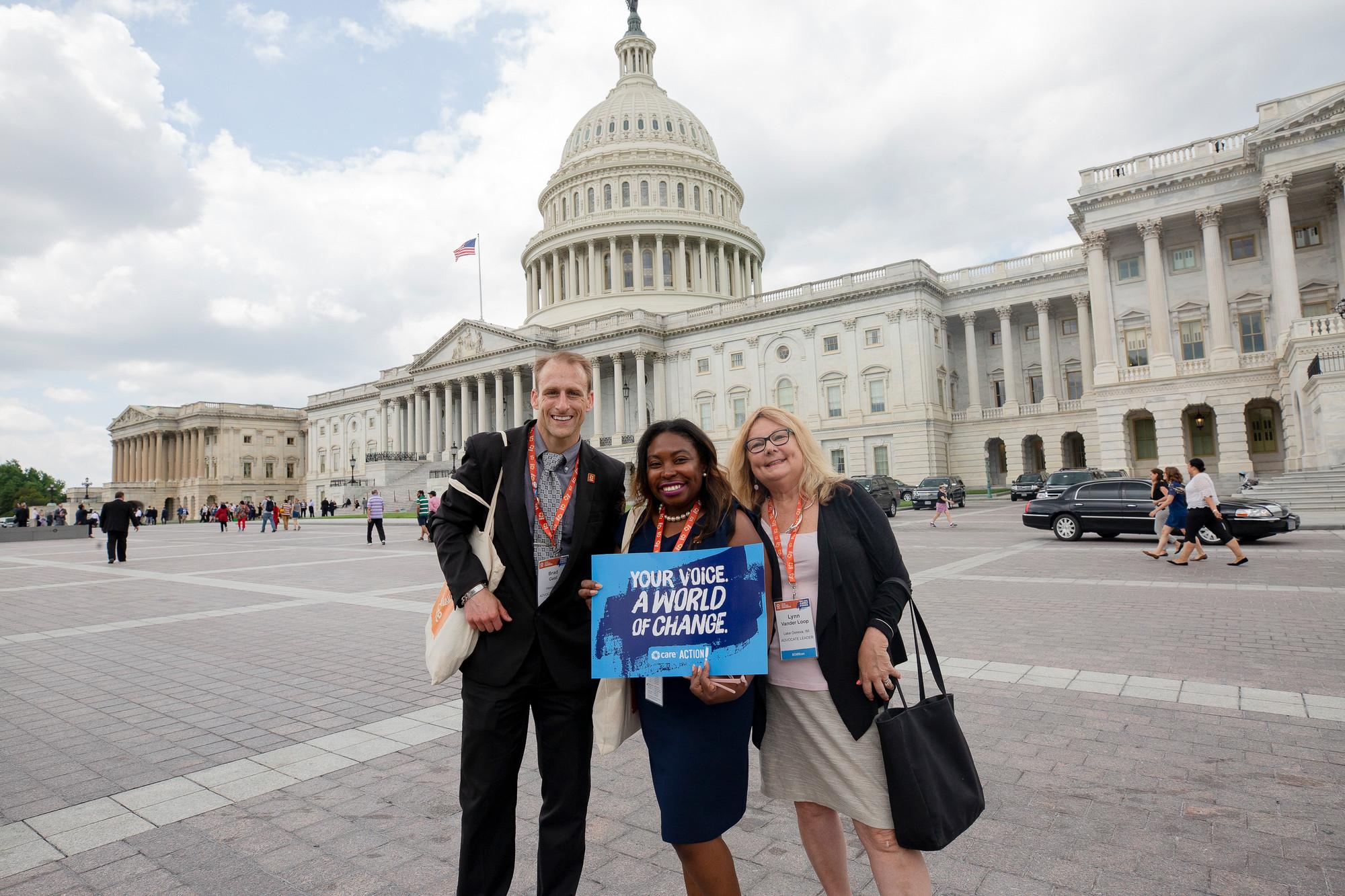 Tres personas se paran frente al Capitolio de los Estados Unidos. Uno sostiene un cartel que dice