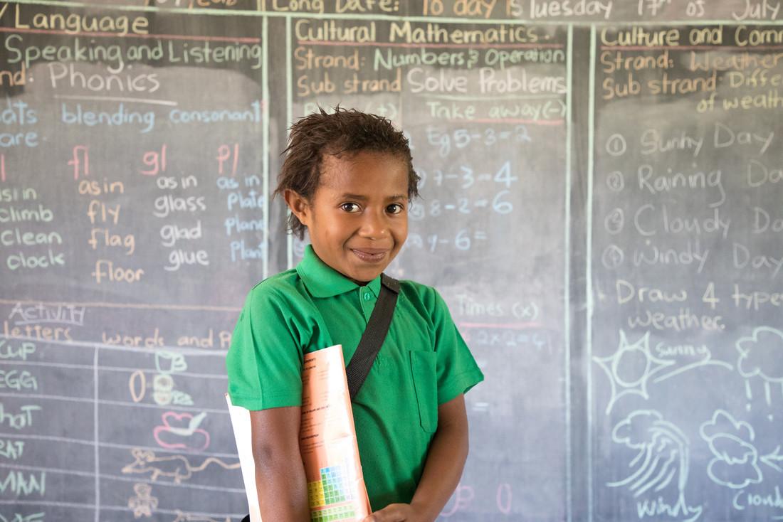 Una niña con una camisa con cuello de color verde brillante sostiene un libro de ejercicios debajo del brazo y se para frente a una pizarra. La pizarra está llena de problemas matemáticos y de ortografía escritos con tizas de diferentes colores.
