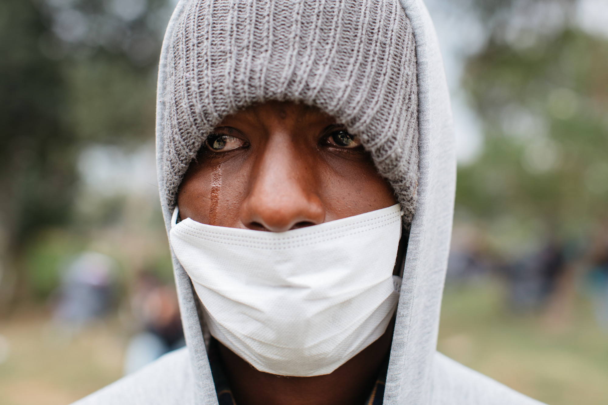 A man with a single tear rolling down his cheek wears a gray stocking hat and a surgical mask over his mouth.