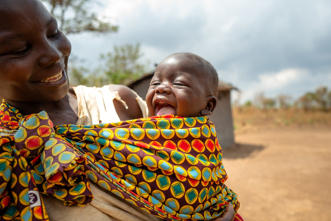 A woman smiles at her baby, who is smiling with his mouth wide open.