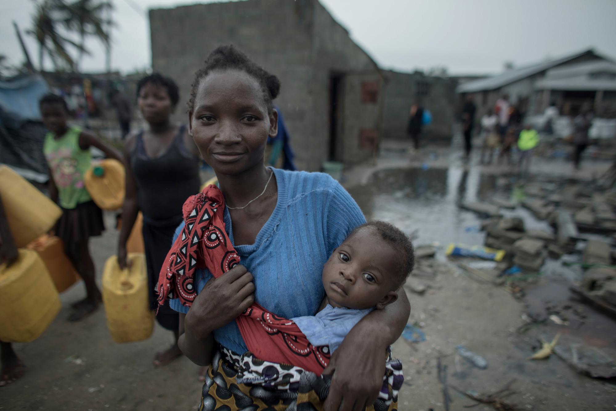 Una mujer en una calle embarrada sostiene a un bebé en un cabestrillo para bebés de un edificio de bloques de hormigón.