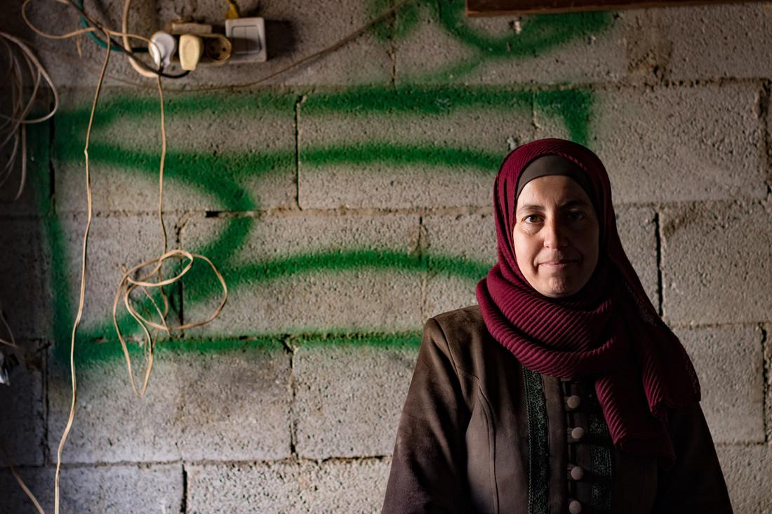 Une femme portant un foulard bordeaux se tient devant un mur de béton marqué de peinture en aérosol verte.