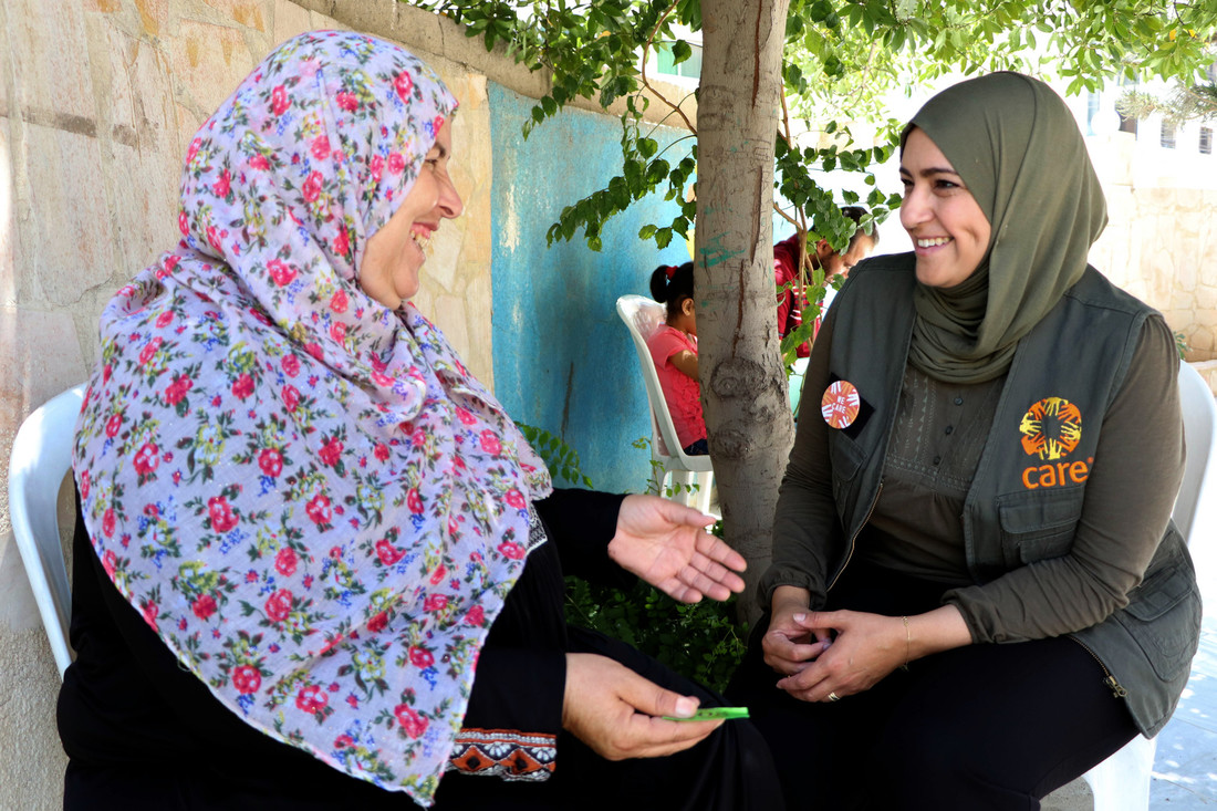 A woman wearing a green head scarf and a black CARE vest sits and speaks with a woman, who is smiling and gesturing with her hands.