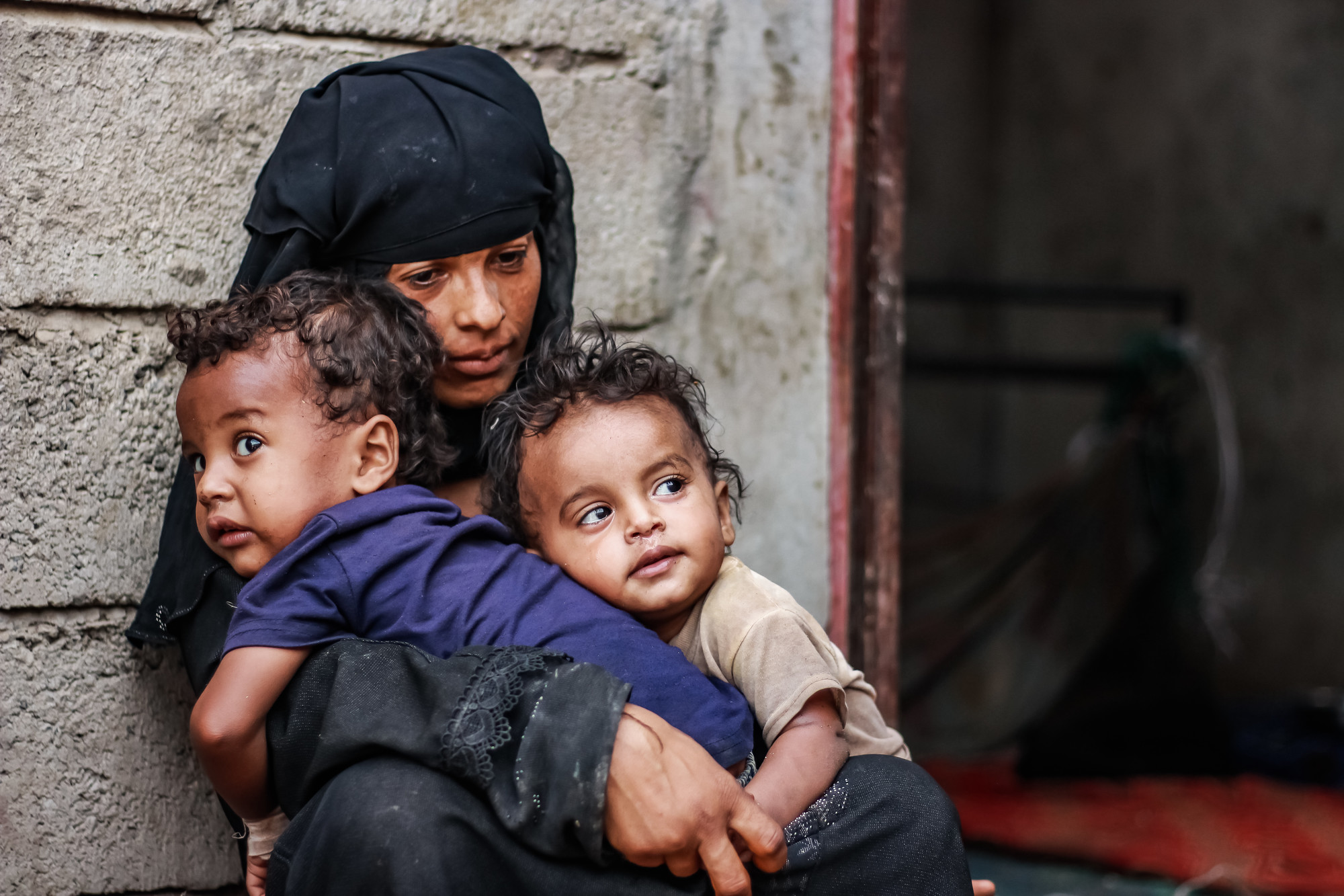 A displaced Yemeni mother of holds two of her children just outside the door of their cinder block home.