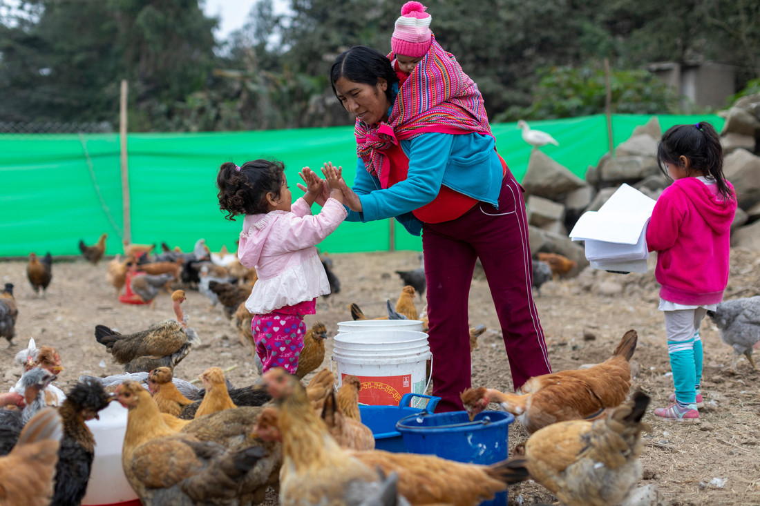 A woman carrying a baby on her shoulders high fives a young girl with both hands. They're surrounded by chickens eating on a farm.
