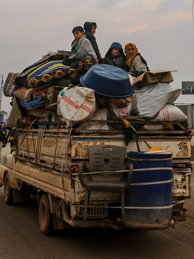 Four people sit on top of a truck overflowing with luggage. A chair and large bucket are tied to the back of the truck, which is driving behind a similarly packed van on a dirt road.