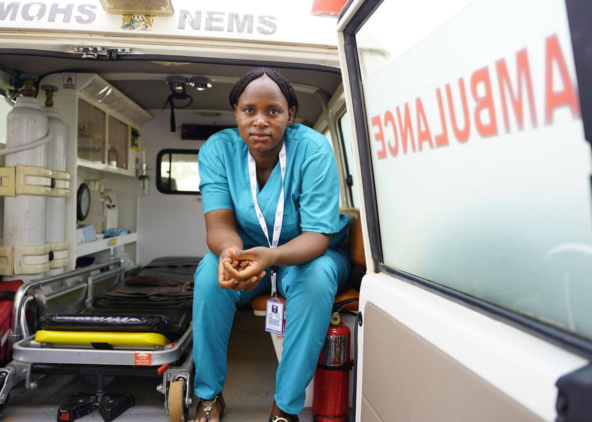 Una mujer vestida con uniformes azules se sienta en la parte trasera de una ambulancia.