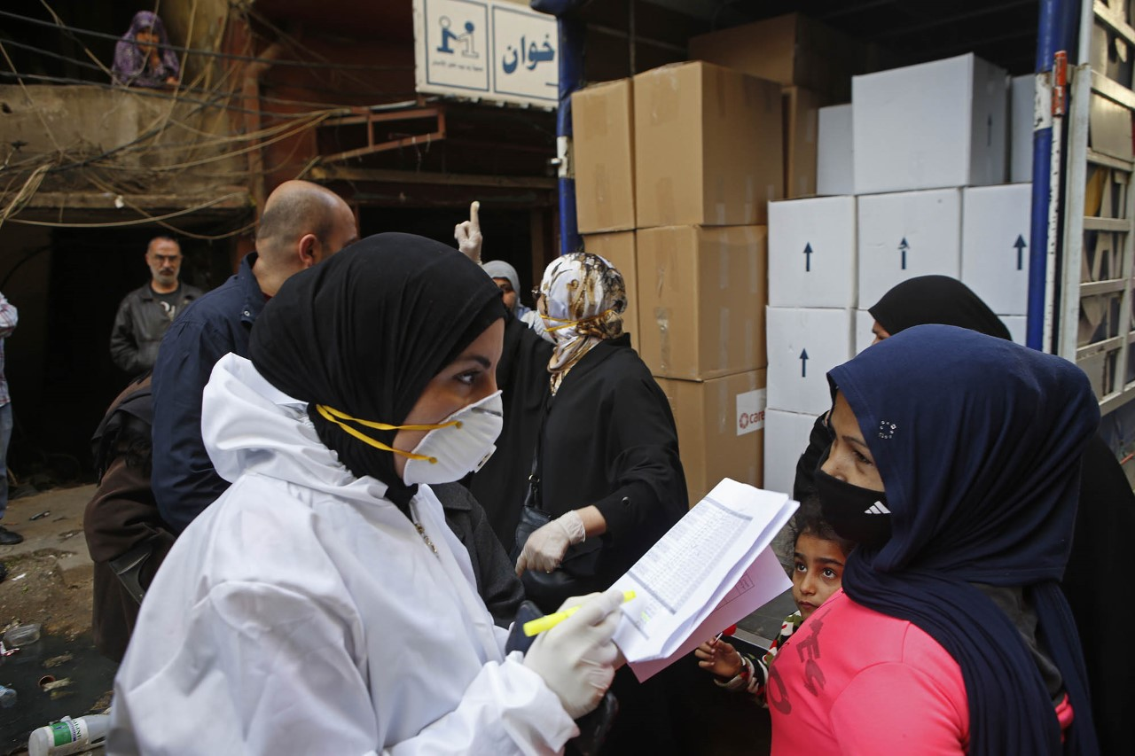 CARE staff in Lebanon dressed in protective gear and masks distribute food parcels and hygiene items from the back of a open box truck.