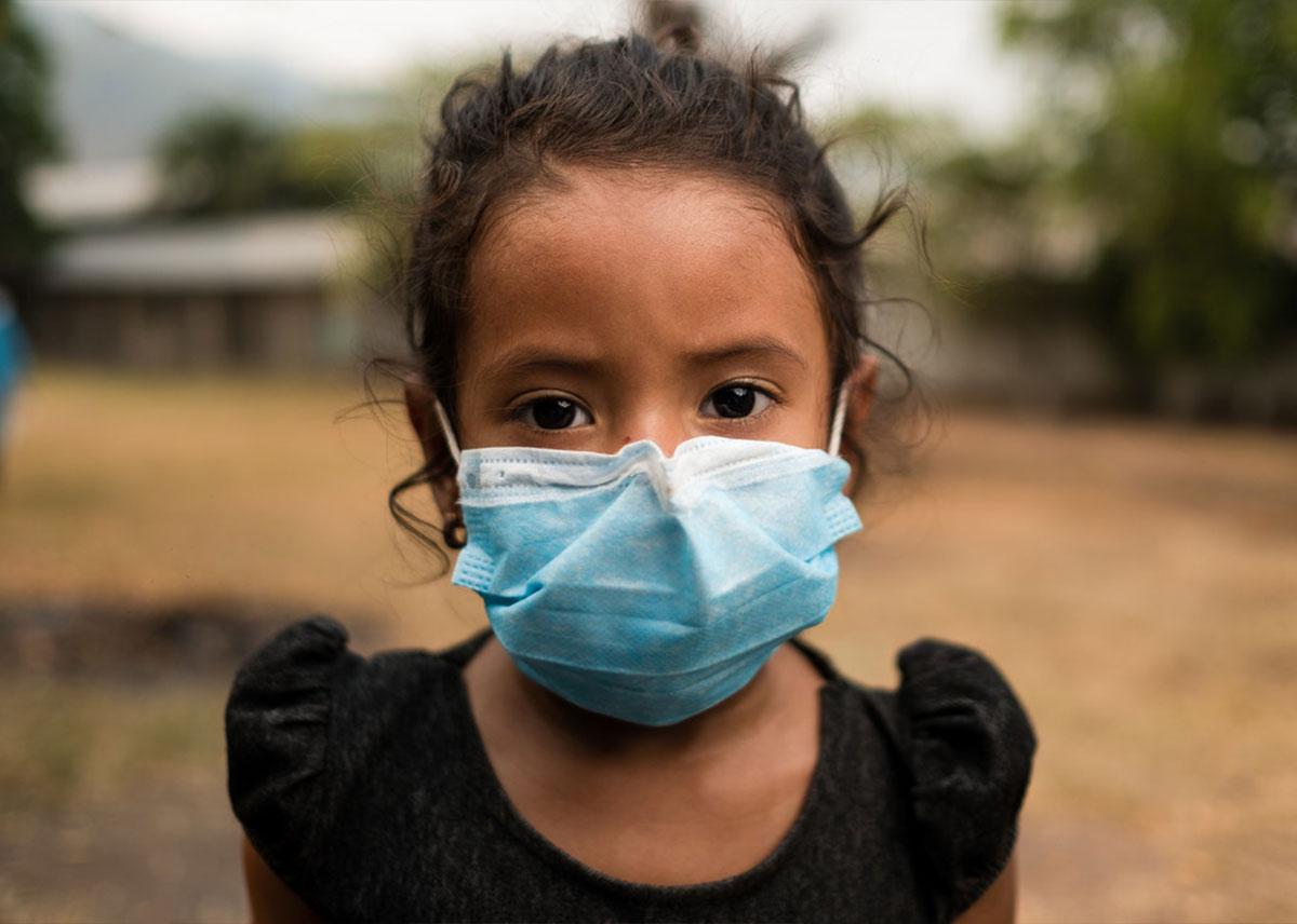 Una niña con una mascarilla azul claro.