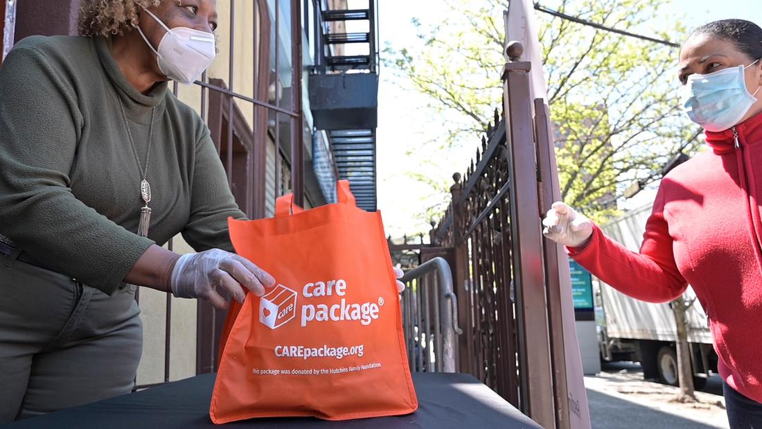 Une femme tend un sac orange étiqueté