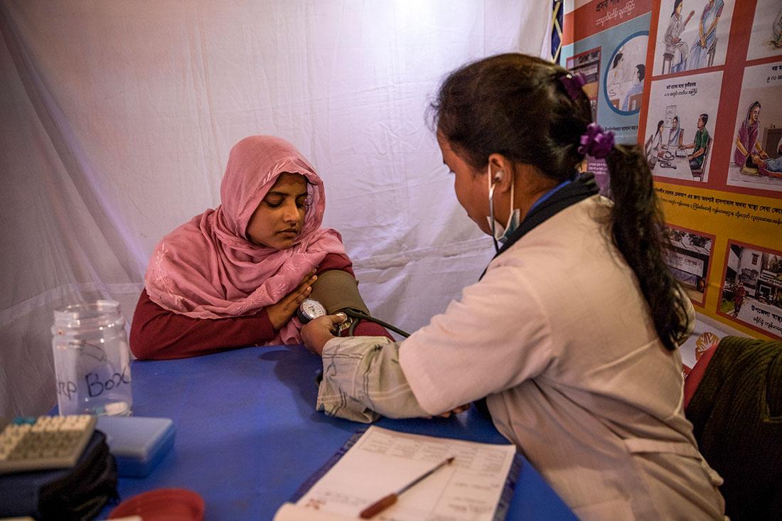 Uma médica mede a pressão arterial de uma mulher sentada à sua frente na mesa.