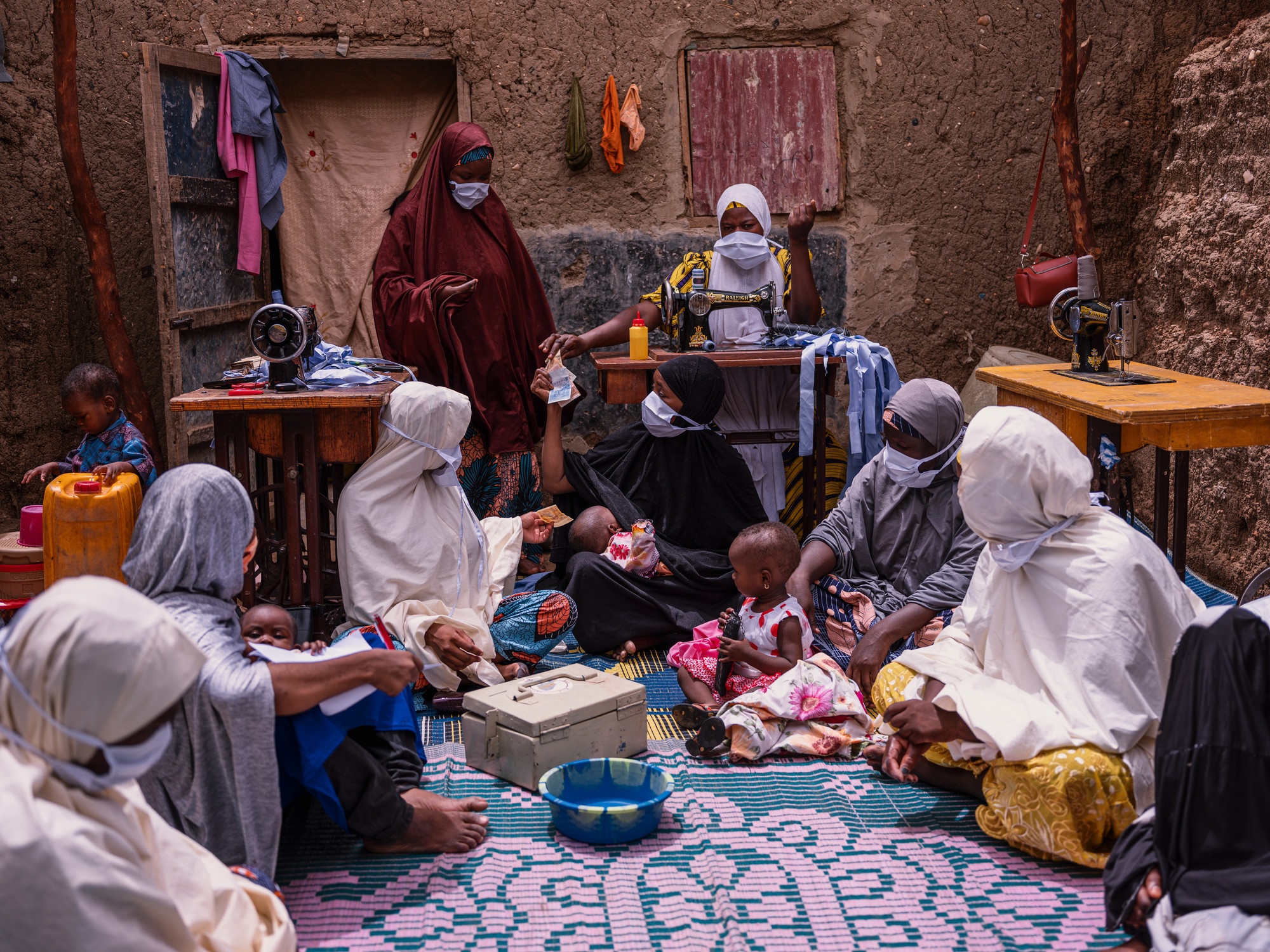 A group of women sit on the floor in front of several tables with sewing machines in Niger. A metal bank box is in the center of the group.