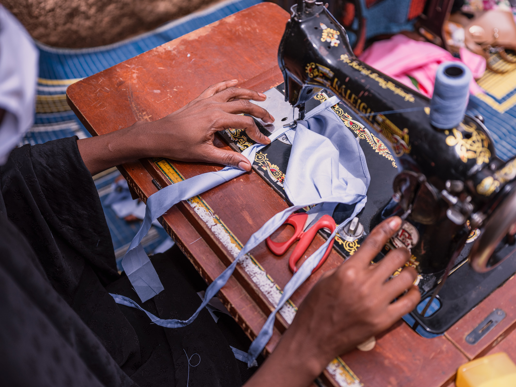 A woman in Niger uses a sewing machine to make a mask.